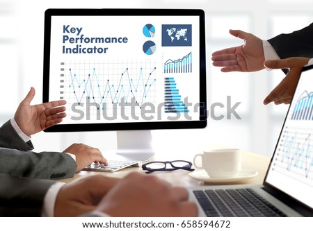 KPI acronym (Key Performance Indicator) Business team hands at work with financial reports and a laptop