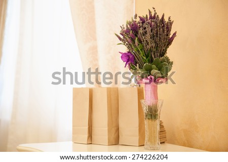 Kraft bags with gifts and wedding bouquet on a table stand. Paper eco bags for food in the restaurant.A row of brown paper bags with a flower bouquet on the table.