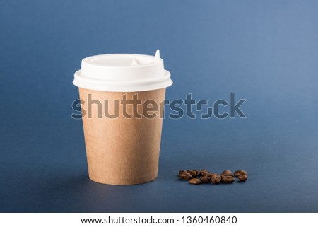 Kraft disposable cup with white cap and coffee beans on a blue background