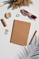 Kraft Paper cover notebook mockup. Feminine stylish desk. Beauty accessories, jewelry and palm leaf shadow. Top view vertical mockup