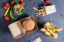 kraft paper food packaging boxes for burgers and  french fries, salad, nagets. on a black background. - image