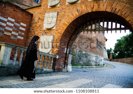 Krakow Poland - August 9, 2011: The nun walks through the entrance gate to the Wawel Castle in Cracow. #1108108811