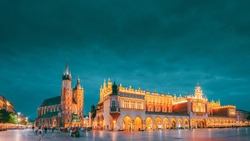 Krakow, Poland. Evening Night View Of St. Mary's Basilica And Cloth Hall Building. Famous Old Landmark Church Of Our Lady Assumed Into Heaven. UNESCO World Heritage Site. Copy Space