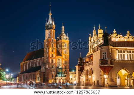 Krakow, Poland. Evening Night View Of The St. Mary's Basilica And Cloth Hall Building. Famous Old Landmark Church Of Our Lady Assumed Into Heaven. Saint Mary's Church. UNESCO World Heritage Site.