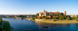 Krakow, Poland. Wide aerial panorama at sunset with Royal Wawel castle and cathedral. Vistula river banks, tourist boats, parks, promenades and walking people
