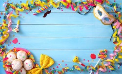 Krapfen, berliner or donuts with streamers, confetti and other party accessoires on blue wooden planks. Colorful carnival or birthday background