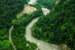 Krasnodar region / Mountain river scenery, top aerial view, national park. Wild nature landscape, green forest with road