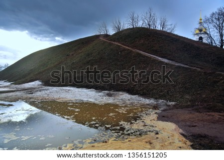 Kremlin in Dmitrow town, Moscow region, Russia. Ancient touristic town. Huge ground hill and belfry of Assumption cathedral. Early springtime photo. Melting snow. #1356151205