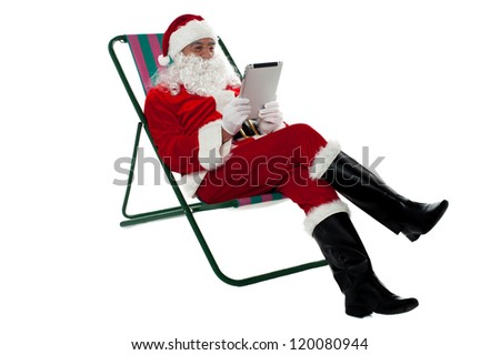 Kris Kringle relaxing on chair and using electronic tablet. Isolated on white.