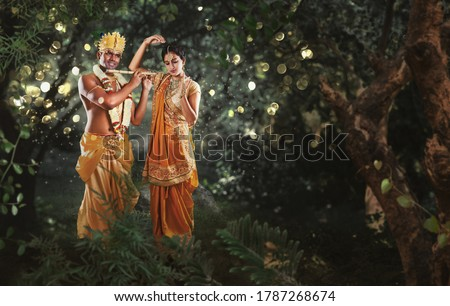 Krishna and Radha in the forest. Full length of Hindu God Krishna playing flute to his beloved Radha Stock photo ©