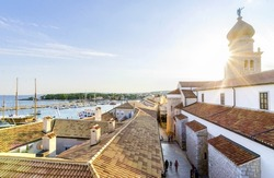 Krk town, Croatia island at sunset. Sun burst through the bell tower of the Church of the Assumption of Blessed Virgin Mary with an angel holding a trumpet, port and ceramic tiles on the roof houses.