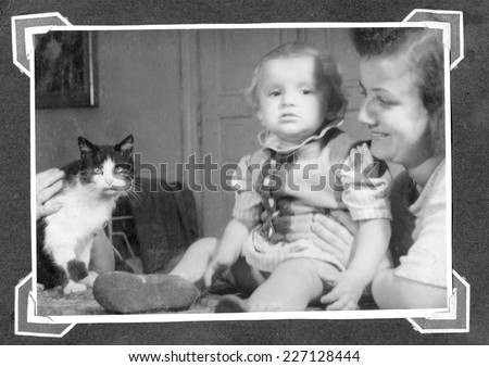 KROSNO,POLAND - CIRCA 1947:vintage photo of baby girl,her mother and cat