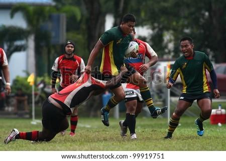 KUALA LUMPUR - APRIL 1:Unidentified ASAS player try to blocks a ATM RAMD player during a Malaysian Rugby Union(MRU) Super League match on April 1, 2012 in Kuala Lumpur, Malaysia. ASAS won 27-25