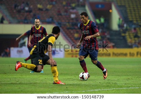 KUALA LUMPUR - AUGUST 10: Barcelona's Adriano (maroon/blue) dribbles past Malaysia's defenders (yellow/black) in a game at the Shah Alam Stadium on August 10, 2013 in Malaysia. Barcelona wins 3-1. - stock photo