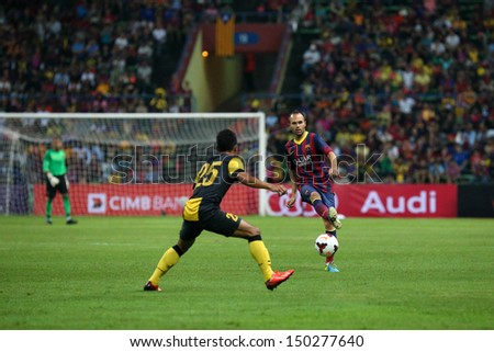KUALA LUMPUR - AUGUST 10: Barcelona 's Andres Iniesta (maroon/blue) passes the ball, watched by Malaysia's WZ Haikal (25) at the Shah Alam Stadium on August 10, 2013 in Malaysia. Barcelona wins 3-1.