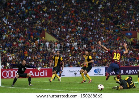 KUALA LUMPUR - AUGUST 10: Barcelona's Jordi Alba (18) is tackled by Malaysia's Aidil Zafuan (fallen) in match at the Shah Alam Stadium on August 10, 2013 in Malaysia. FC Barcelona wins 3-1.