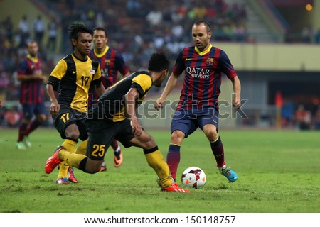 KUALA LUMPUR - AUGUST 10: FC Barcelona's Andres Iniesta (maroon/blue) dribbles the ball in a friendly match vs Malaysia at the Shah Alam Stadium on August 10, 2013 in Malaysia. Barcelona wins 3-1.