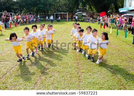 KUALA LUMPUR - AUGUST 15 : Unidentified children doing a teamwork racing at Taman Midah Kindergarten sport day on 15 August, 2010 in Kuala Lumpur Malaysia. - stock photo