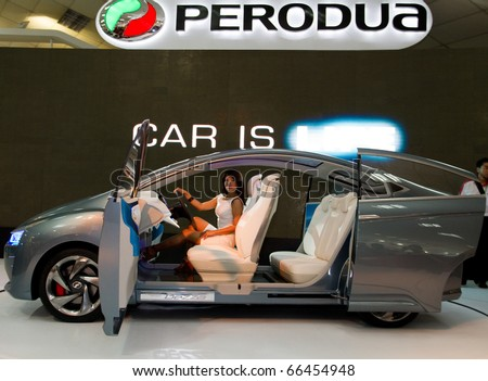 KUALA LUMPUR - DEC 03: An Asian model poses with Perodua Bezza, a concept car which launched at the Kuala Lumpur International Motorshow 2010  on December 3, 2010 in Kuala Lumpur, Malaysia