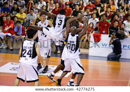 KUALA LUMPUR - DECEMBER 13: KL Dragons' Chris Kuete blocks an attempt by Thailand Tigers' Ikenna Nwankwo in the ASEAN Basketball League match. December 13, 2009 in Kuala Lumpur.