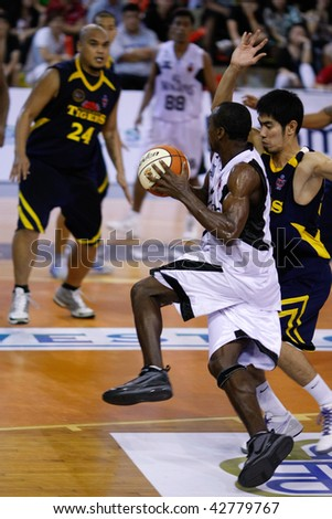 KUALA LUMPUR - DECEMBER 13: KL Dragons' Chris Kuete (2nd R) powers in to score in this match against Thailand Tigers in the ASEAN Basketball League match December 13, 2009 in Kuala Lumpur.
