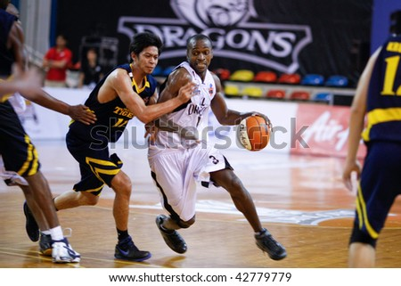 KUALA LUMPUR - DECEMBER 13: KL Dragons' Chris Kuete (R) rushes into the paint in this match against Thailand Tigers in the ASEAN Basketball League match December 13, 2009 in Kuala Lumpur.
