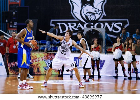 KUALA LUMPUR - JANUARY 05: KL Dragons' Li Wei (33) defends an attack by Satria Muda BritAma's Miller at the ASEAN Basketball League match January 05, 2010 in Kuala Lumpur.