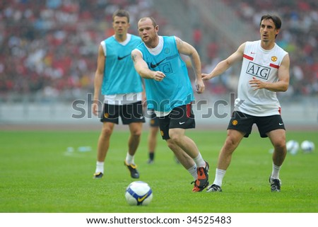 KUALA LUMPUR - JULY 17: Michael Carrick (L) Wayne Rooney (C) and Gary Neville (R) of Manchester United team warms up before friendly match against Malaysia XI team at National Stadium, Kuala Lumpur.