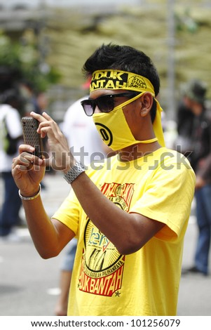 KUALA LUMPUR, MALAYSIA - APRIL 28: A protester with a smartphone at the protest rally organized by the coalition for clean and fair election on April 28, 2012 in Dataran Merdeka, Kuala Lumpur Malaysia