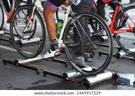 KUALA LUMPUR, MALAYSIA -APRIL 18, 2015: Bicycle riders are using the cycling roller trainer before the race begins. This equipment can help riders to warm up. #1469917229