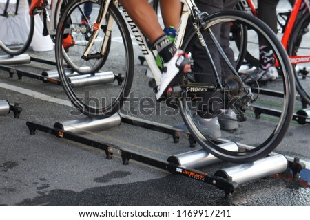 KUALA LUMPUR, MALAYSIA -APRIL 18, 2015: Bicycle riders are using the cycling roller trainer before the race begins. This equipment can help riders to warm up. #1469917241