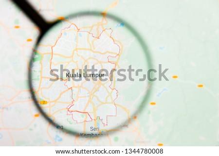 Kuala Lumpur, Malaysia city visualization illustrative concept on display screen through magnifying glass #1344780008
