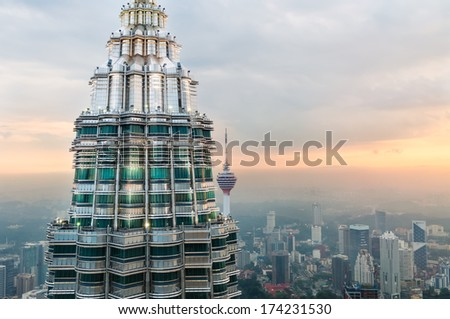KUALA LUMPUR MALAYSIA DECEMBER 26 The setting sun gleams off of the second Petronas Tower and KL Tower in the distance Photo taken December 26 2013 in Kuala Lumpur Malaysia