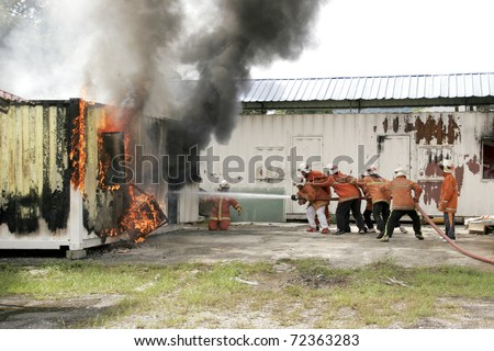 KUALA LUMPUR, MALAYSIA - FEB 23: Participants with the guidance from Fire and Rescue Department put out a fire during a Fire Awareness and Safety Day on February 23, 2011 in Kuala Lumpur, Malaysia