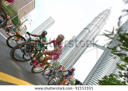 KUALA LUMPUR, MALAYSIA-FEBRUARY 15: Cyclists pedal their way in front of the iconic KLCC building landmark during the Le Tour de Langkawi competition in Kuala Lumpur,Malaysia on February 15,2009.