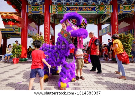 KUALA LUMPUR, MALAYSIA - FEBRUARY 2019 : People do not miss the opportunity to touch and give Ang Pow during Chinese New Year Lion Dance performances at Thean Hou Temple. #1314583037