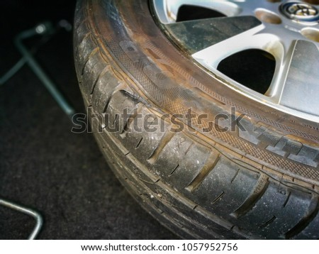 Kuala Lumpur Malaysia-3.2.2018:Image of apparent 1-inch torn hole on a punctured tire still attached to rim. Selective focus on torn. Soft focus due to low light condition in car boot. #1057952756