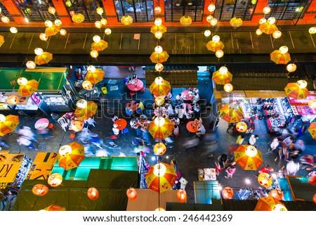 Kuala Lumpur, Malaysia - 27 July, 2014: People eating at the tables and walking along the street at Kuala Lumpur\'s Chinatown at night, view from above, Kuala Lumpur on July 27, 2014.