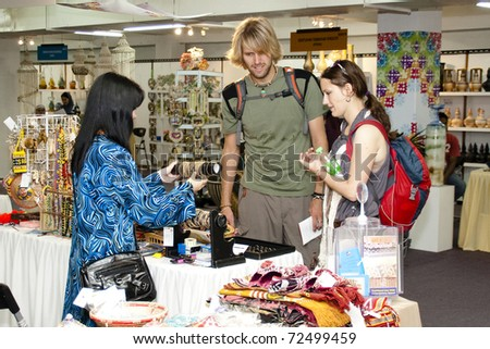 KUALA LUMPUR, MALAYSIA - MARCH 4: A tourist couples make a selection of handmade craf  at the Malaysia National Craft Day 2011 on March 4, 2011 in Kuala Lumpur, Malaysia.