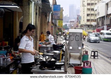 KUALA LUMPUR, MALAYSIA - MARCH 17: Local man cooks fast food on the street in Kuala Lumpur's Chinatown on March 17, 2011 in Kuala Lumpur. KL Chinatown is popular tourist attraction and a food haven - stock photo