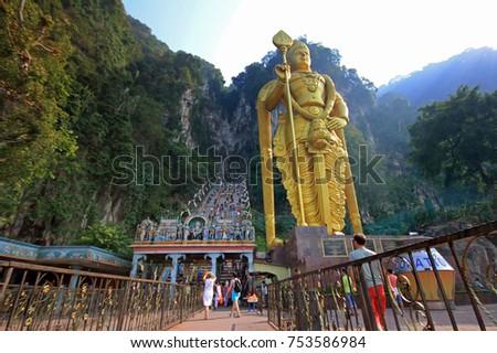 KUALA LUMPUR, MALAYSIA - 09 March 2014: People visiting Batu Caves in Kuala Lumpur city. Giant Murugan statue at the entrance of Batu Caves, Malaysia. #753586984