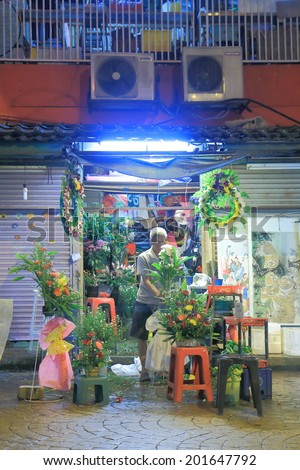 KUALA LUMPUR MALAYSIA - 30 May, 2014: Unidentified man sells flowers in China Town. China town, also known as Petaling street is a popular tourist destination and has dozens of restaurants.