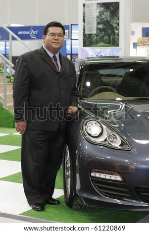 KUALA LUMPUR, MALAYSIA - MEI 18 : A young businessman posed next to a Porsche Panamera S is on display during the 6th World Islamic Economic Forum (WIEF) Mei 18, 2010 in Kuala Lumpur Malaysia. - stock photo