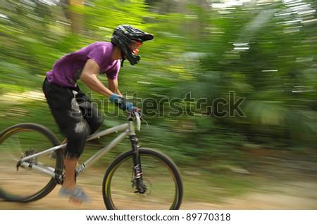 KUALA LUMPUR, MALAYSIA - NOVEMBER 27: Unidentified competitor in a downhill mountain bike race.Panning Action. Bicycle Fest 2011 in Kuala Lumpur, Malaysia  on November  27, 2011.