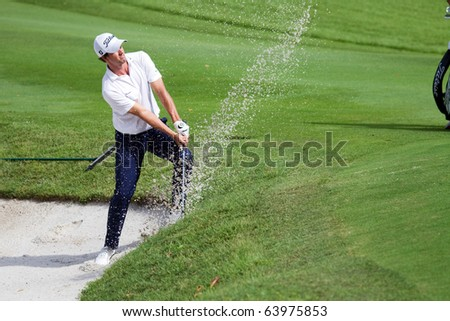 KUALA LUMPUR, MALAYSIA - OCTOBER 29: Australian Adam Scott chips out of the bunker on Day 2 of the CIMB Asia Pacific Golf Classic on October 29, 2010 in Kuala Lumpur, Malaysia