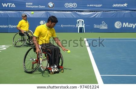 KUALA LUMPUR - MARCH 4: Malaysia Olympic Wheelchair players Abu Samah Borhan and Che Abu bakar Mat serves during a skilled performance show at the BMW Malaysian Open on March 4, 2012 in Kuala Lumpur, Malaysia.