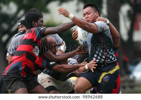 KUALA LUMPUR-MARCH 31: Three SAHOCA players try to tackle an UiTM Lions player during a Malaysian Rugby Union Super League 2012 match (UiTM Lions vs SAHOCA) on March 31,2012 in Kuala Lumpur,Malaysia