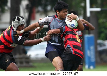 KUALA LUMPUR-MARCH 31: Two unidentified SAHOCA players try to tackle an UiTM Lions player during a Malaysian Rugby Union Super League 2012 match (UiTM Lions vs SAHOCA) on March 31, 2012 in Kuala Lumpur, Malaysia