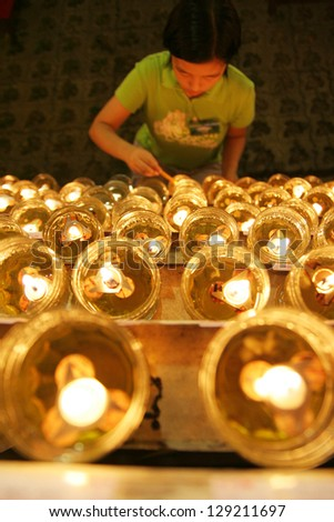 KUALA LUMPUR - MAY 18: Unidentified girl lights up candles during the celebration of Wesak day on May 18, 2008 in Kuala Lumpur, Malaysia. Wesak is informally called as Buddha's Birthday.