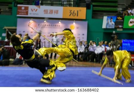 KUALA LUMPUR - NOV 05: Hong Kong\'s dalian team performs a fight scene in the Men\'s Dual Event at the 12th World Wushu Championship on November 05, 2013 in Kuala Lumpur, Malaysia.